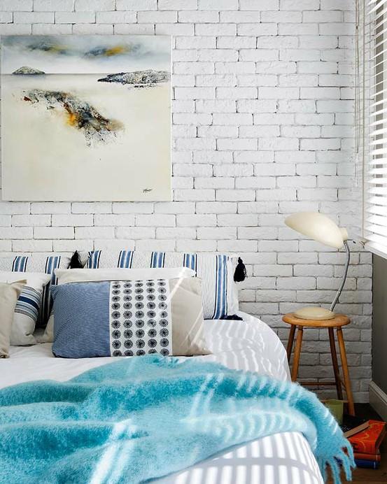witte stenen muur in beach look slaapkamer met aqua blauwe details en plaid en schilderij