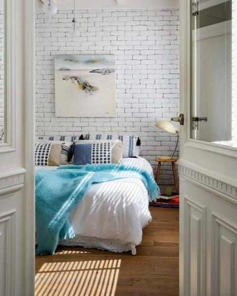 witte stenen muur in beach look slaapkamer met aqua blauwe details en plaid