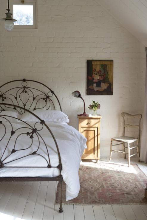 witte stenen muur in landelijke slaapkamer met oud stalen bed en oud roze kleed