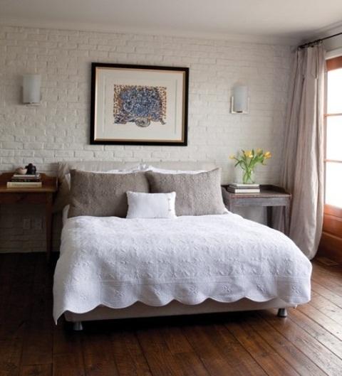 witte stenen muur in slaapkamer met gezellig landelijk ontwerp met schilderij aan de muur
